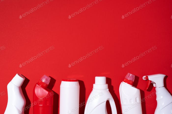 Cleaning products on red background. Copy space. Top view. Flat lay. Plastic waste. Detergent bottle