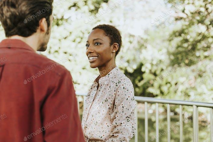 Mann im Gespräch mit einer schwarzen Dame in einem Park