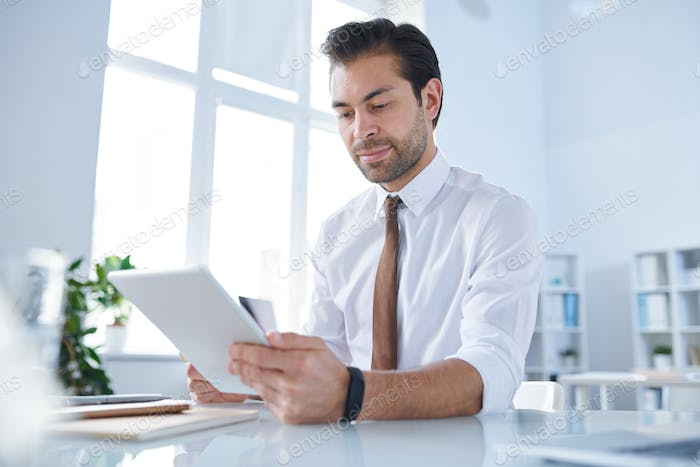 Young businessman with tablet analyzing data in the net