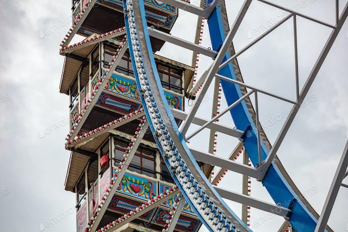 Ferris wheel closeup detail view on cloudy sky. Oktoberfest, Bavaria, Germany