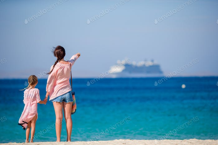Young beautiful mother and her adorable little daughter at tropical beach looking at the sea