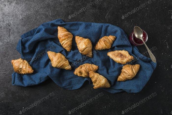 Frisch gebackene französische Croissants mit einem Glas Marmelade auf schwarzem Hintergrund mit einer dunkelblauen Serviette.