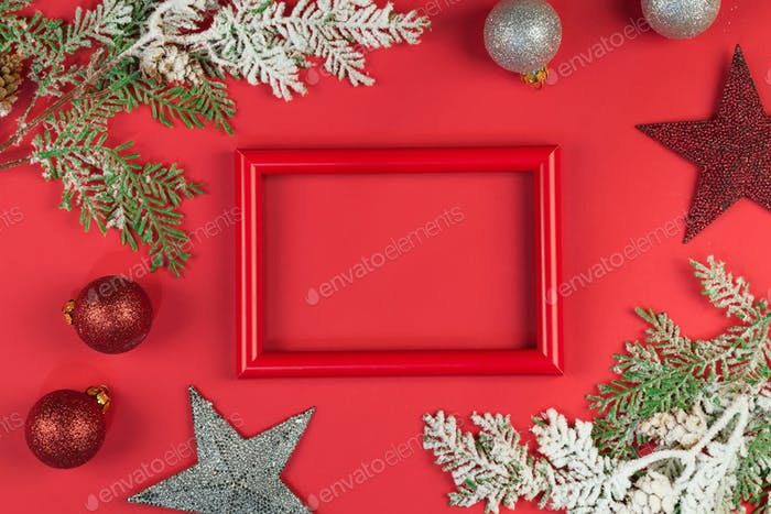 Red photo frame with brances in the snow, christmas toys on red background, copy space