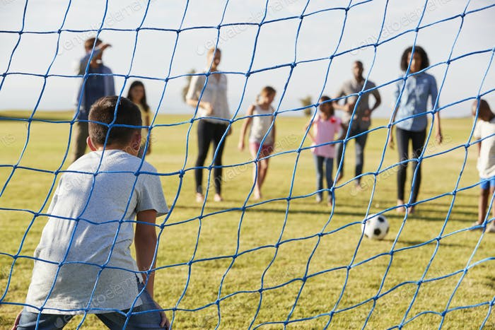 Boy defending goal during a family football game