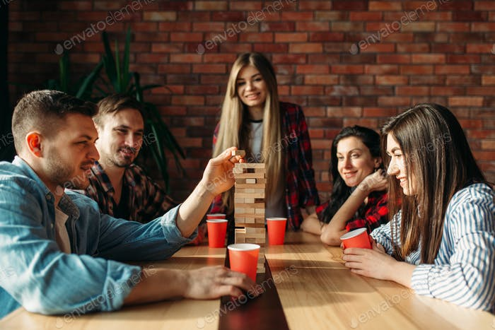 Friends plays table game, selective focus on tower