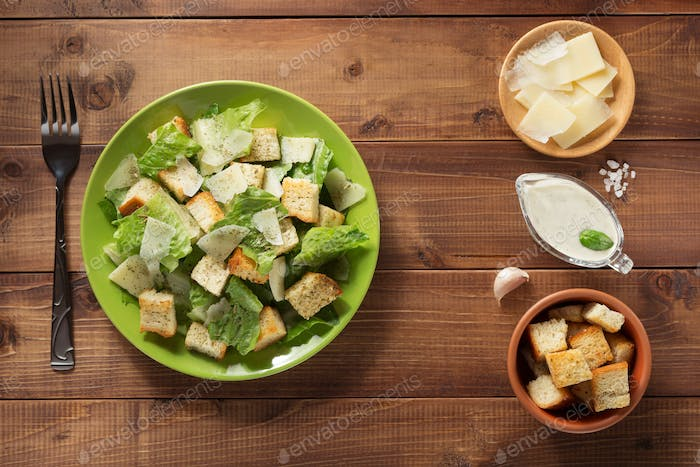 caesar salad and ingredients at wood