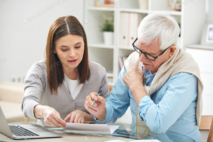 Young female explaining her senior father how to fill in paper