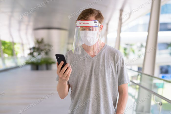 Young man using phone with mask and face shield for protection from corona virus outbreak in the