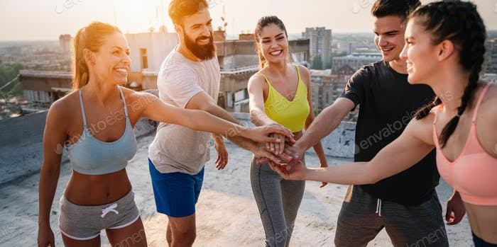 Group of happy friends or sportsmen exercising outdoor