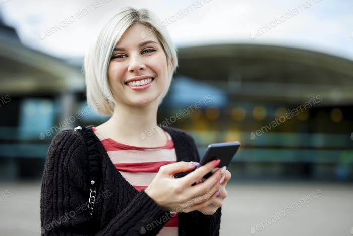 Woman Smiling While Using Mobile Phone Outside Train Station