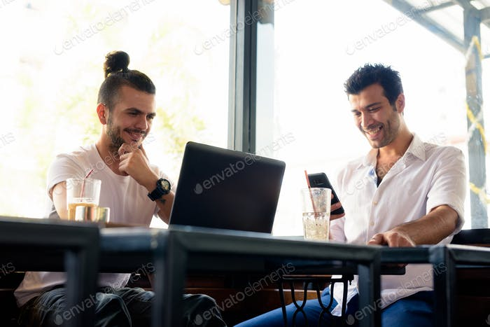 Two happy men as friends thinking and working together at the coffee shop