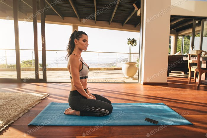 Beautiful young woman sitting in yoga pose at home