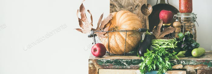 Autumn food ingredients and utensils over wooden cupboard, wide composition
