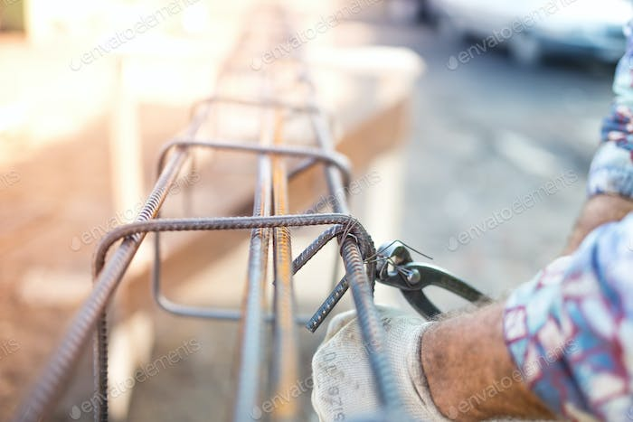 Details of infrastructure - Construction worker hands securing steel bars with wire rod for concrete