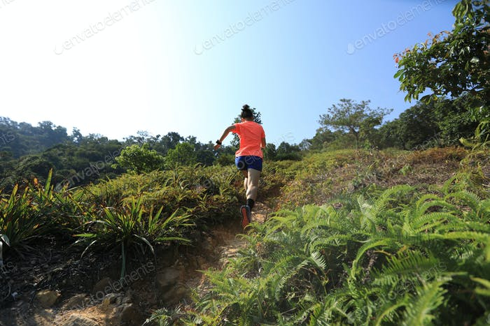 Woman trail runner running to mountain top
