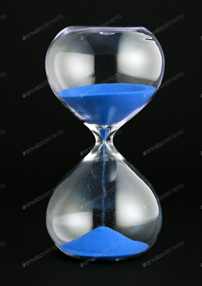 Close-up of a transparent hourglass with blue sand