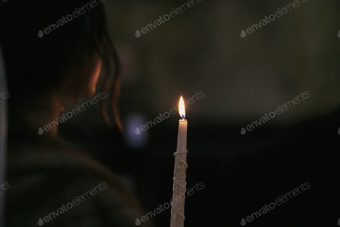 candle light in the dark in church. bride holding candle fire during holy matrimony in church