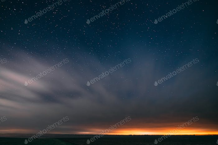 Night Starry Sky With Glowing Stars Above Countryside Landscape. Light Cloudiness Overcast Above