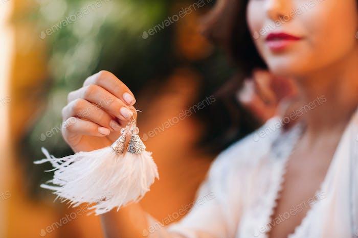 Ohrringe mit weißen Fransen in den Händen der Braut bei einer Hochzeit in Italien.Hochzeit Ohrringe weiß