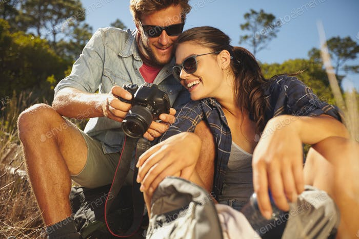 Smiling couple on a hike looking pictures on digital camera