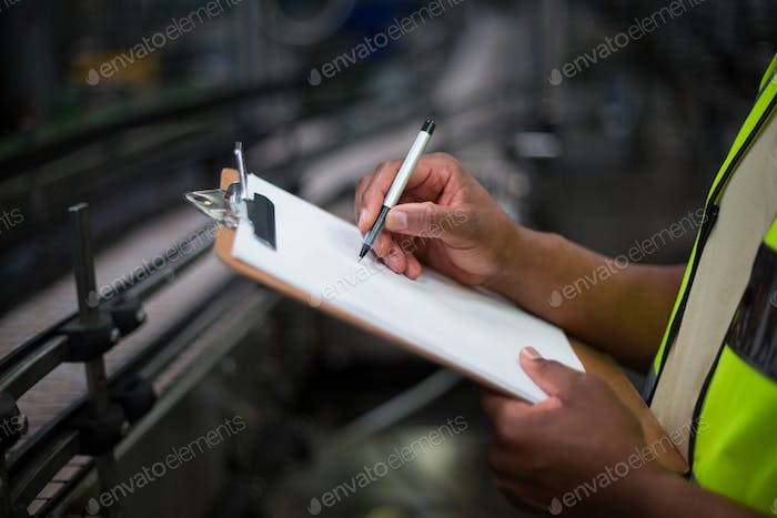 Factory worker writing on notepad in factory