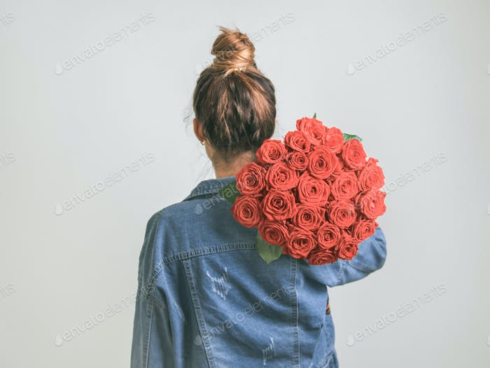 Back view of woman, holding Living Coral roses