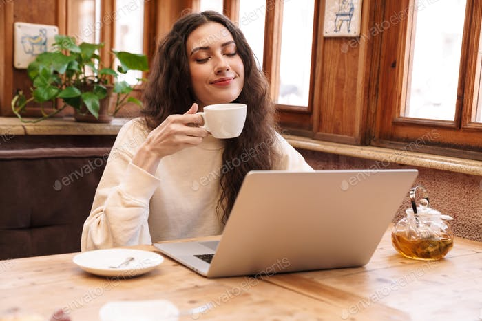 Image of smiling young woman using laptop and drinking tea in cozy cafe