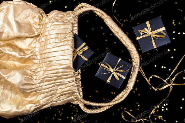 Black gift boxes with gold ribbon pop