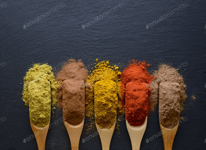 colorful herbs and spices in wooden spoons