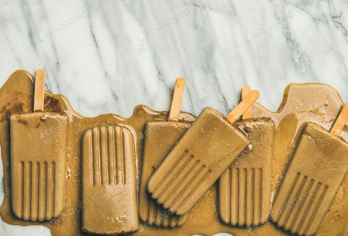 Flatlay of melting coffee latte popsicles, grey background, copy space