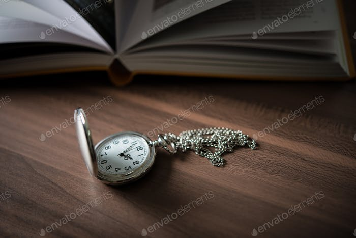 Close up of golden pocket watch lean on pile of book.