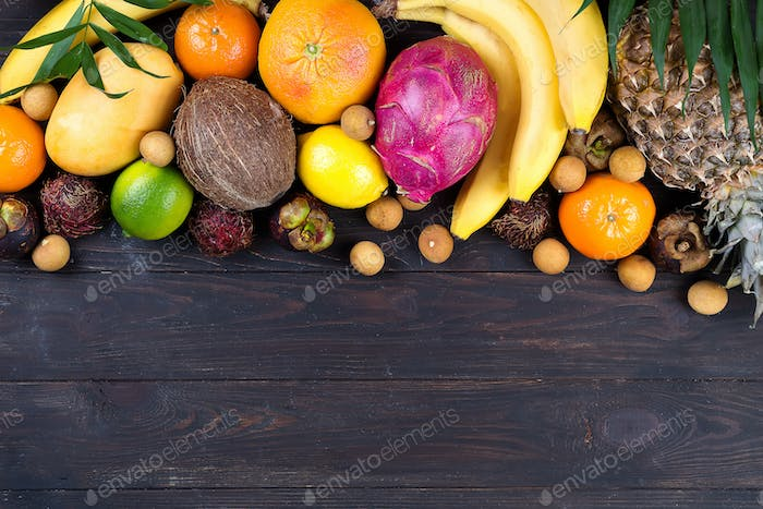 Healthy rainbow tropical fruits frame with palm leaves on blue wooden table, top view, copy space