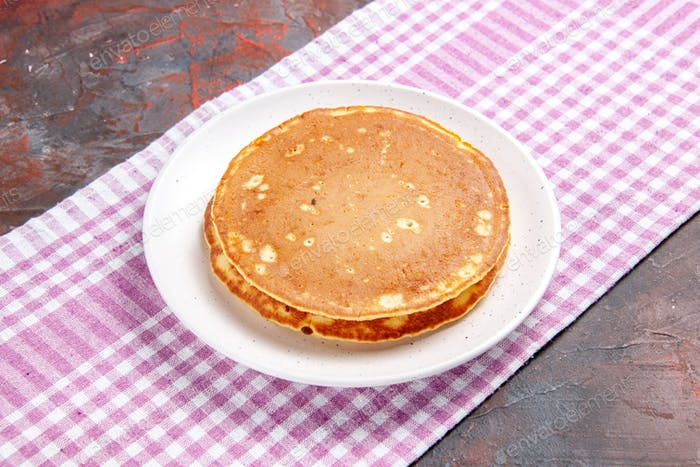 Delicious pancakes on a pink stripped towel on mixed color background