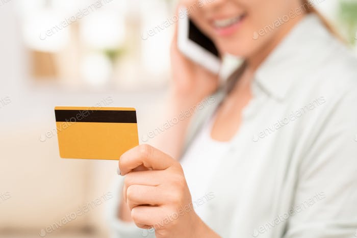 Yellow plastic card with black magnet line in hand of young female consumer