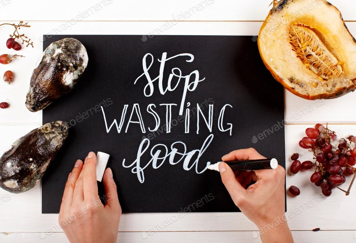 Woman writing on a chalkboard Stop wasting food lettering