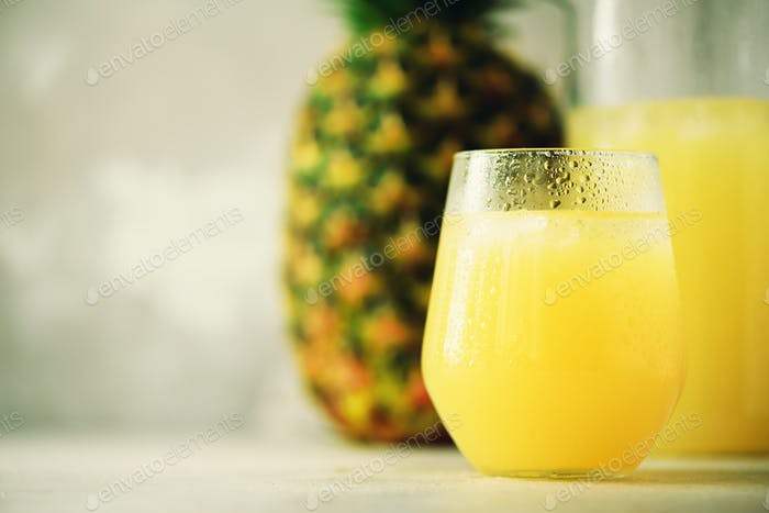 Pineapple juice in glassware and whole pineapple fruit on gray background. Copy space, sunlight