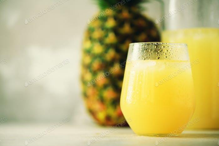 Ananassaft in Glaswaren und ganze Ananasfrucht auf grauem Hintergrund. Kopierraum, Sonnenlicht