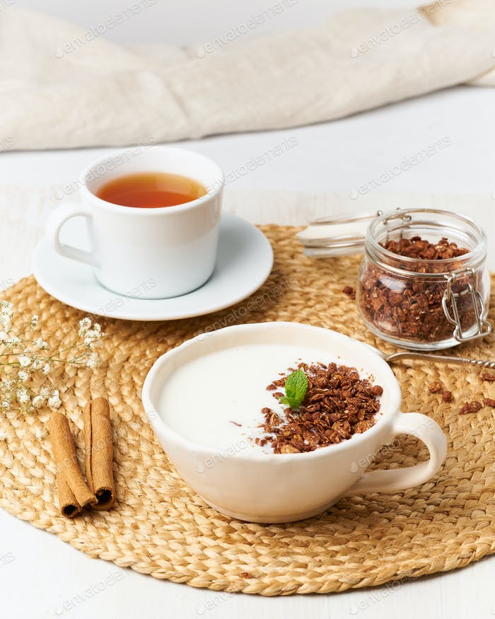 Yogurt with chocolate granola in cup, breakfast with tea on beige background, side view, vertical.