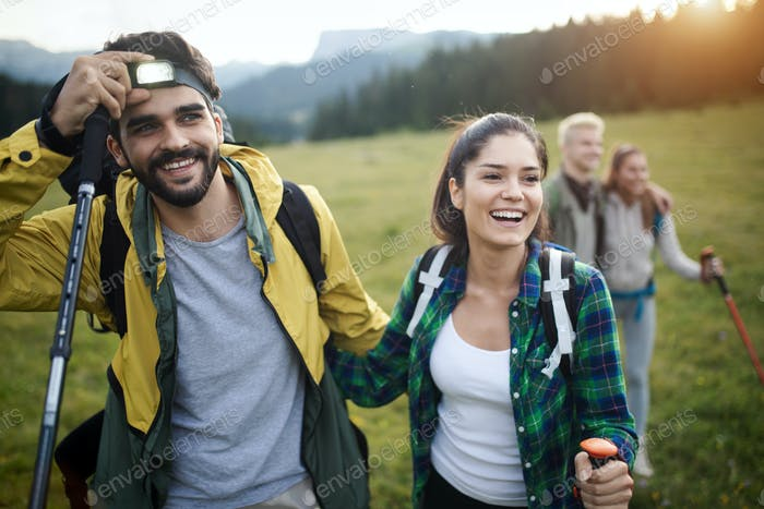 Group of hikers with backpacks and sticks walking on mountain. Friends making an excursion