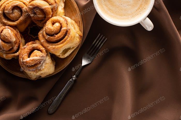 Top View of Fresh Homemade Cinnamon Rolls on Plate Near Coffee And Fork on Silk Brown Cloth