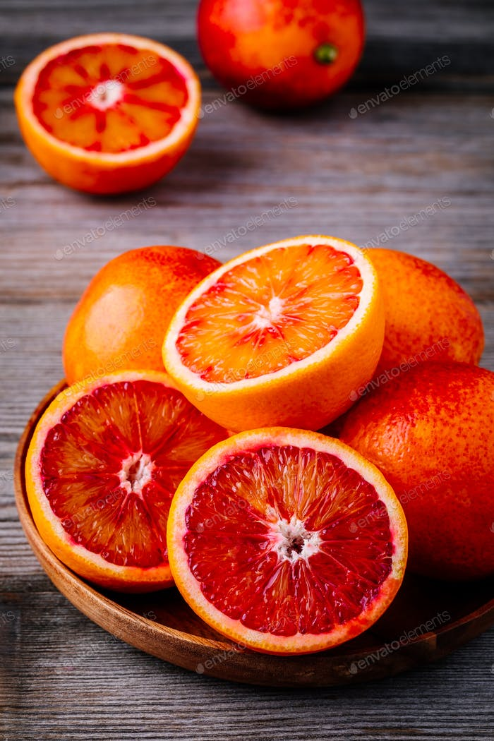 Sliced and whole ripe juicy Sicilian Blood oranges on wooden background.
