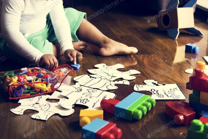 African descent kid enjoying puzzles on wooden floor