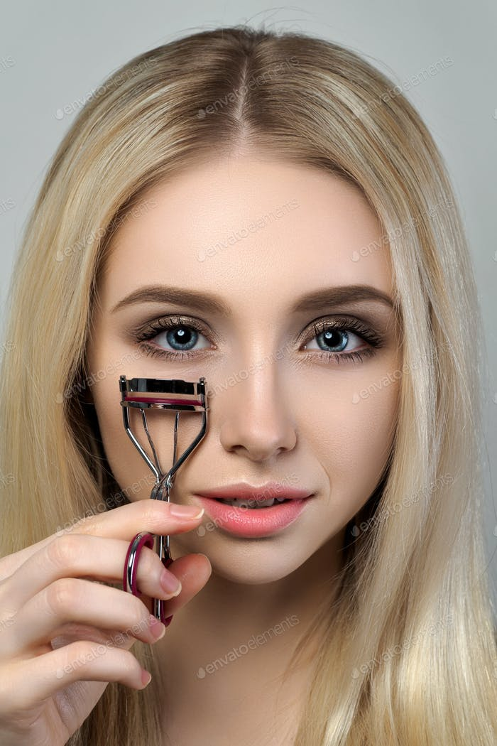 Young beautiful woman holding eyelash curler
