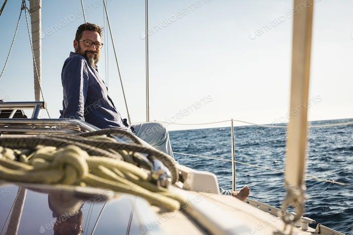 Erwachsener Mann setzt sich auf das Segelbootdeck und genießt die Reise - Reise-Lifestyle-Leute auf der Yacht
