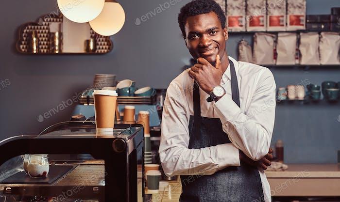 Красивый африканский бариста в кафе.