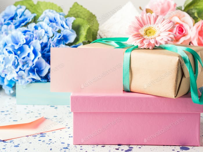 Blank pink card and stacked gift boxes. Flowers