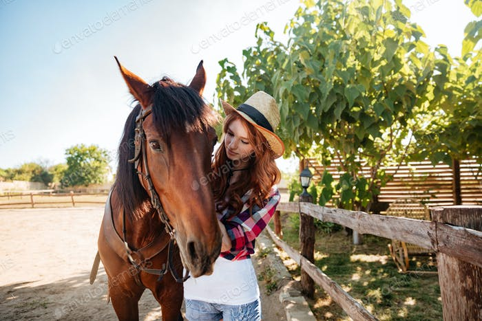 Redhead woman cowgirl taking care of her horse on farm