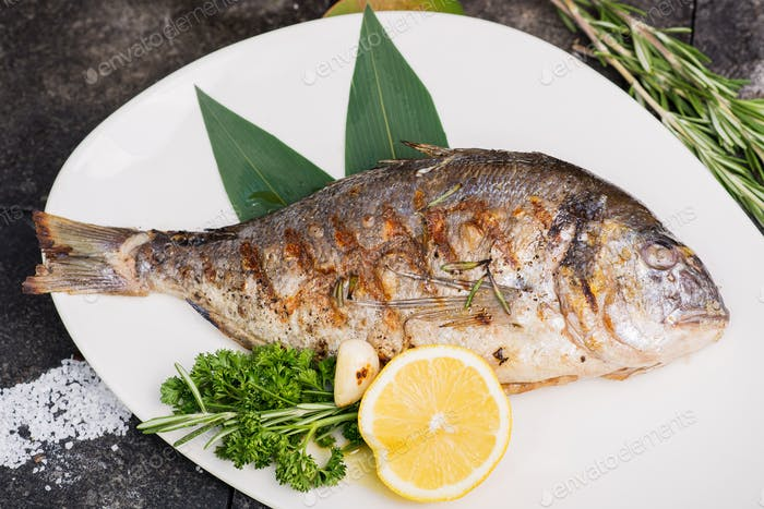 cooking process dorado fish grilled fried fish served on a white plate with lemon and greens