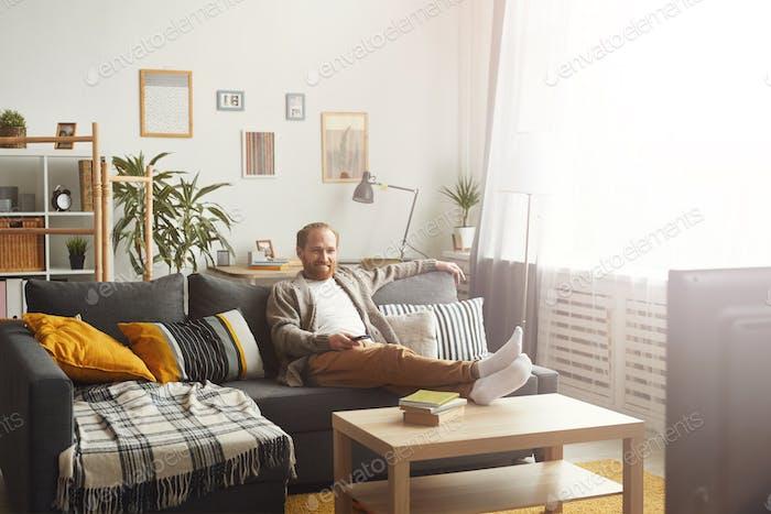 Smiling Man Watching TV at Home