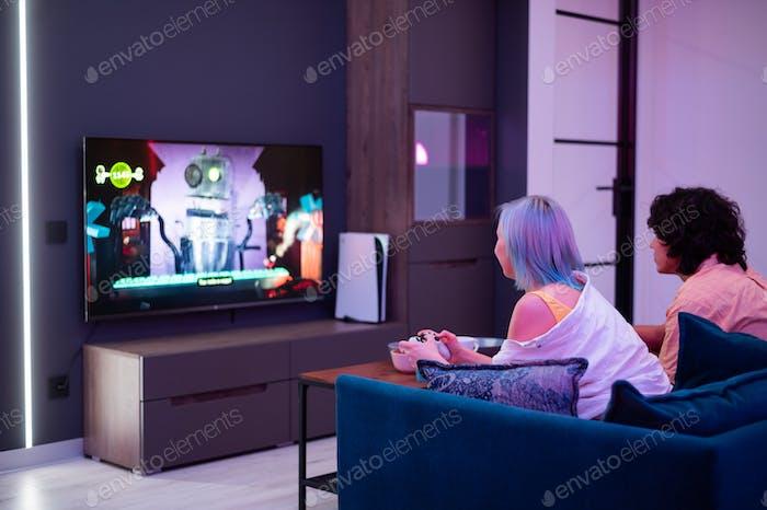 Young adult couple boy and girl playing video game console, having fun, back view